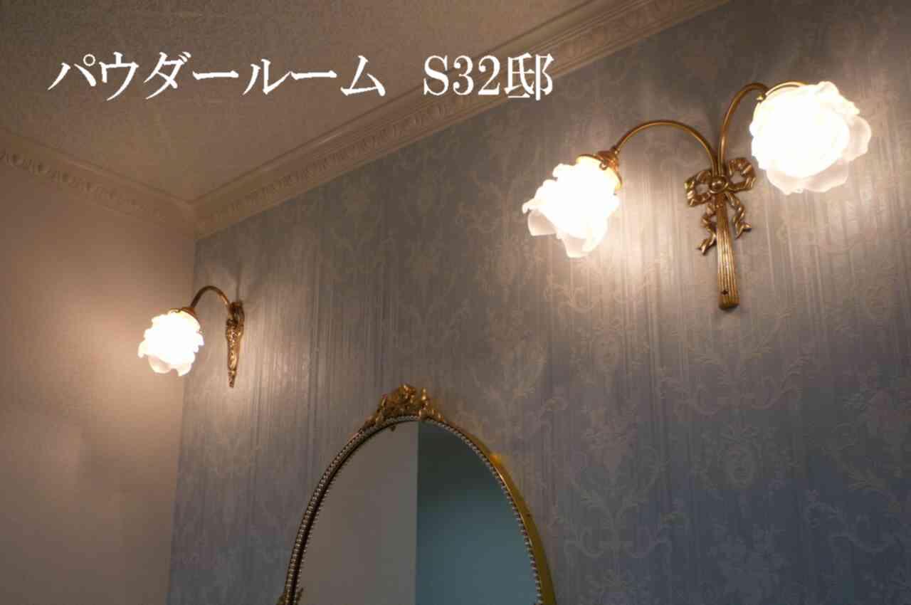 パウダールームの壁に薔薇の花をモチーフにしたブラケットライトを