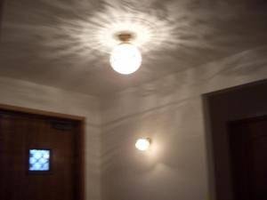 アンティーク調の天井灯が壁の小さなバラのブラケットライトとともに設置されている