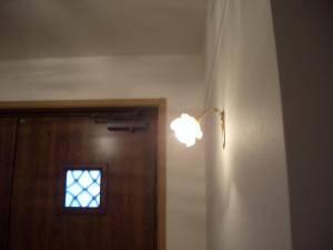 バラの形のガラスシェードをもつブラケットライトを玄関の照明用に設置