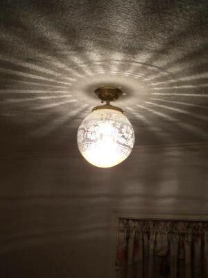 玄関ホールの天井に綺麗な光の模様を映し出すアンティーク調の照明