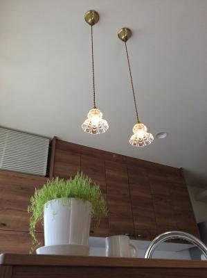 小さなガラスのペンダントライト2本が対面キッチンの上に下がります