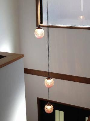 玄関の吹き抜け用の照明-3連のアンティーク風ペンダントライトを2階から見下ろした施工例写真