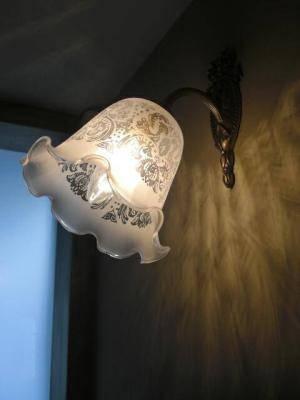 玄関に使われたアンティーク調のブラケットライトはエッチング入りのガラスシェードを使っています