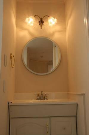 アンティーク調でリボンのデザインのブラケットライトを洗面所の照明として鏡の上に設置