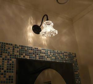 洗面所のタイルで囲われた鏡のための小さなブラケット照明