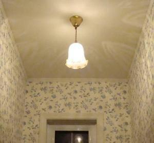 壁紙の美しいトイレの天井にアンティーク調のペンダントライトを設置したら、天井に光の模様が広がりました