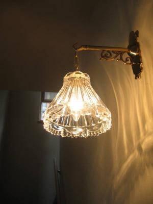 居間に入る前に見上げて楽しめるクラシックな壁照明
