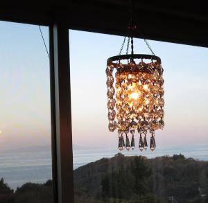 アンティーク調のクリスタルシャンデリアが海の夕景をバックに灯されている