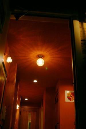 赤い玄関にコーディネートされた天井灯と壁つけ灯